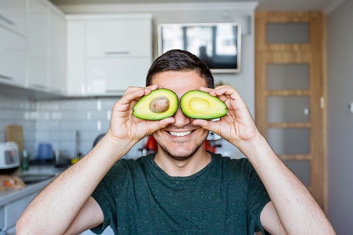 Young man having fun with avocado at the kitchen - gettyimageskorea