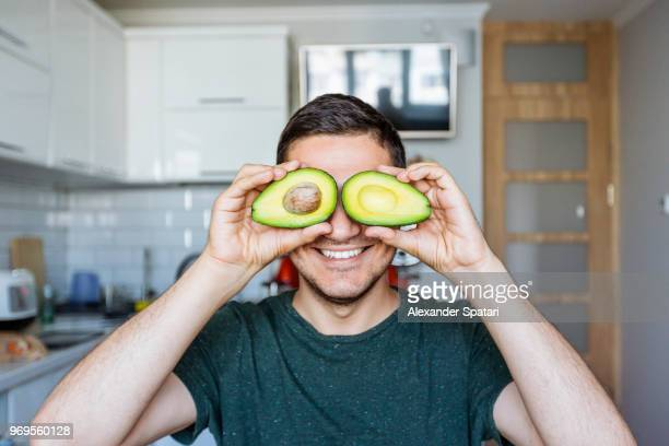young man having fun with avocado at the kitchen - vegana fotografías e imágenes de stock