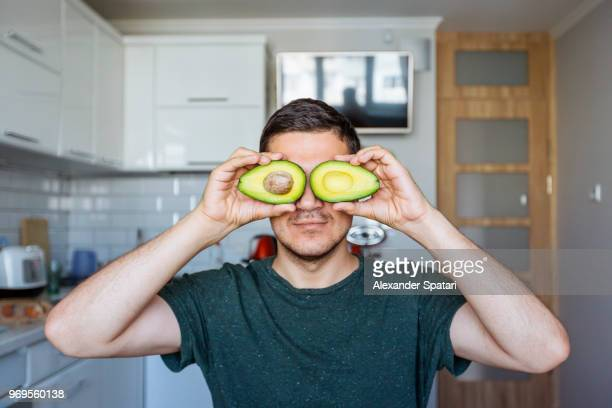 Young man having fun with avocado at the kitchen