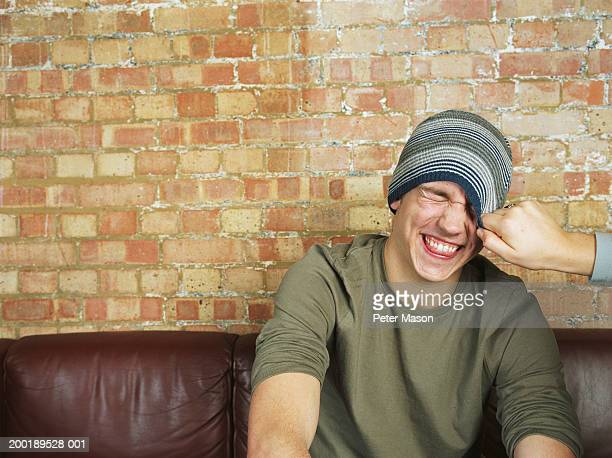 young man having hat pulled down over face, smiling - 16 17 anos imagens e fotografias de stock