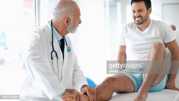 young man having his ankle examined. - male feet stock photos and pictures