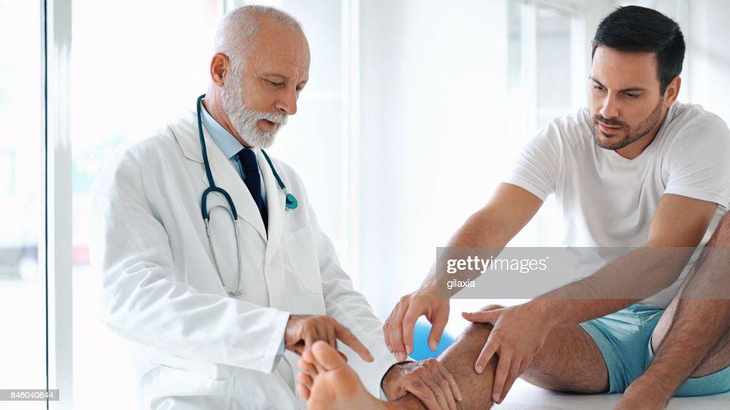 Hombre joven tener el tobillo examinado. : Foto de stock