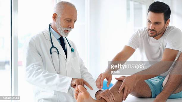Young man having his ankle examined.