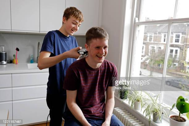 A young man having his hair cut at home by a teenage boy.