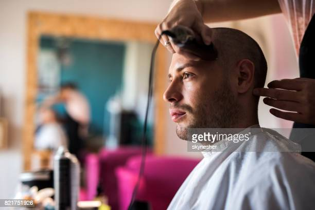 Young man having his head shaved with electric razor at barber shop.