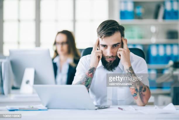 jongeman, problemen op het werk, handen op het hoofd - hopeloosheid stockfoto's en -beelden