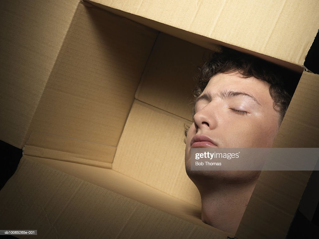 Young man head in cardboard box, eyes closed : Foto stock