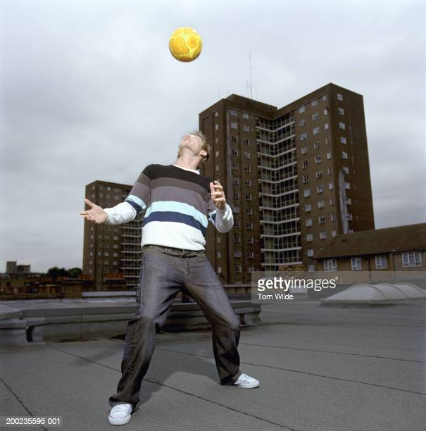 young man heading football on rooftop - heading stock pictures, royalty-free photos & images