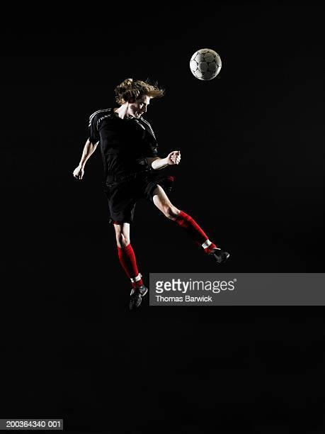 young man heading soccer ball - defensa jugador de fútbol fotografías e imágenes de stock