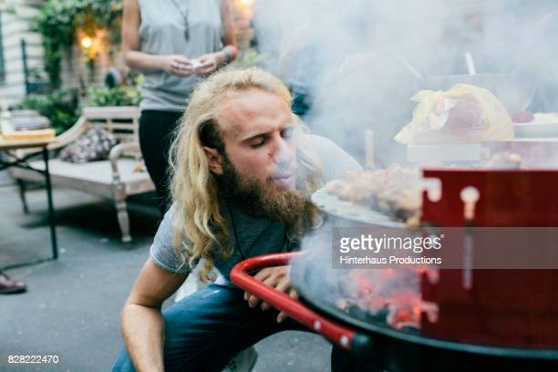 young man heating up barbecue at party - grillen stock-fotos und bilder