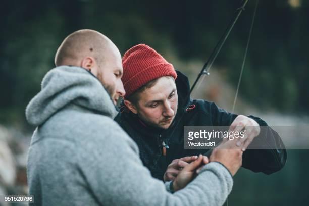 young man helping friend with fishing rod - angeln stock-fotos und bilder