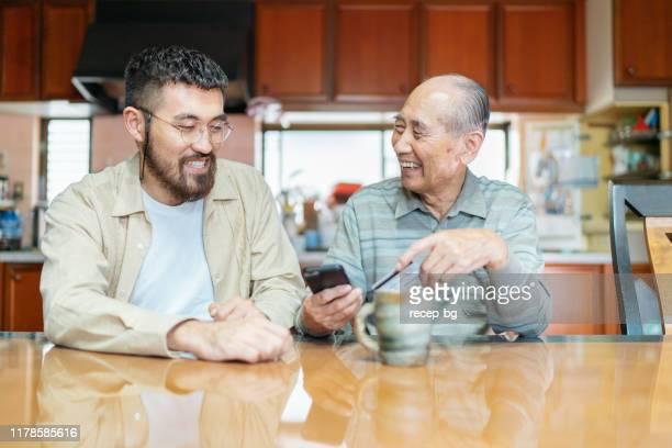 オンラインショッピングで彼の祖父を助ける若い男 - 祖父 ストックフォトと画像