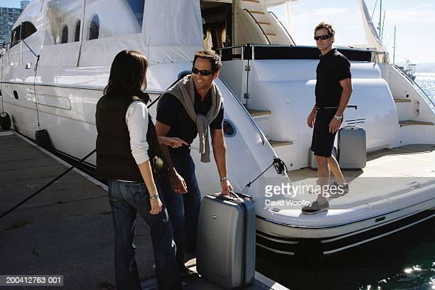 若い男性のカップルのお荷物のサポートをロードし、ヨットのマリーナ - 乗員 ストックフォトと画像