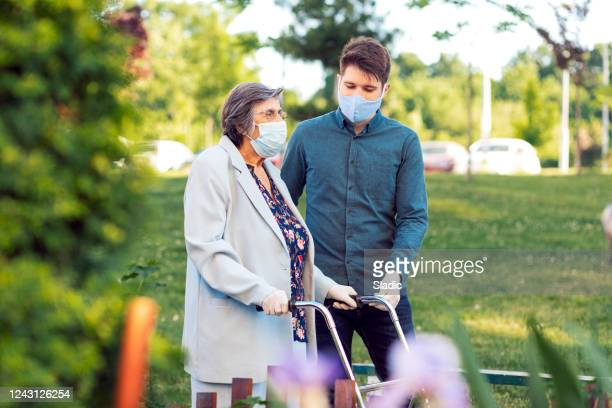 young man helping senior woman walking in the street - assistance stock pictures, royalty-free photos & images