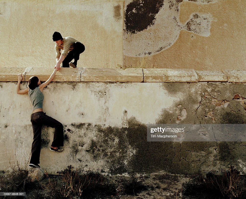 Young man helping young woman over wall : Stock Photo