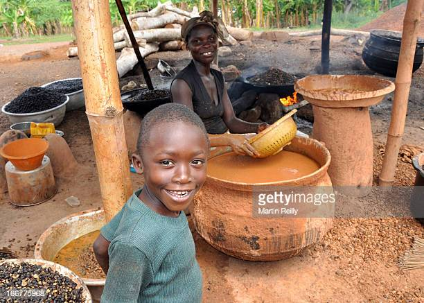 Young man helps his mother with the production of Palm Nut Oil in rural Ghana. Like many villages in Africa the women are the main providers as most...