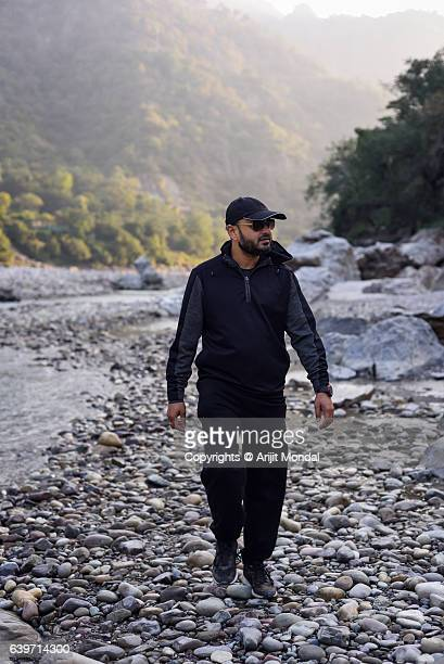 Young man hiking and exploring river area of the Ganga at Rishikesh