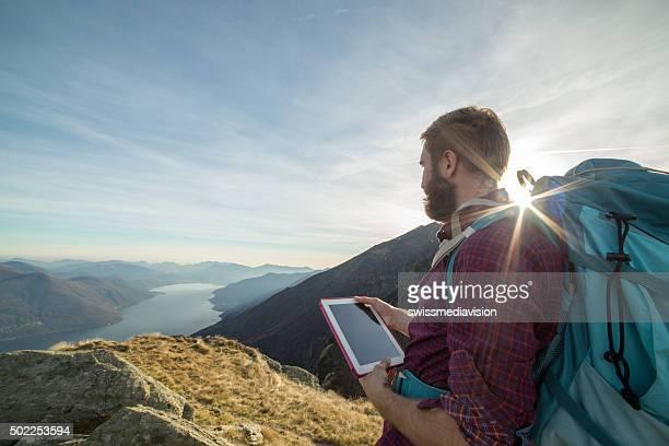若い男性のハイキングマップを使用して、実施、デジタルタブレットを持っている