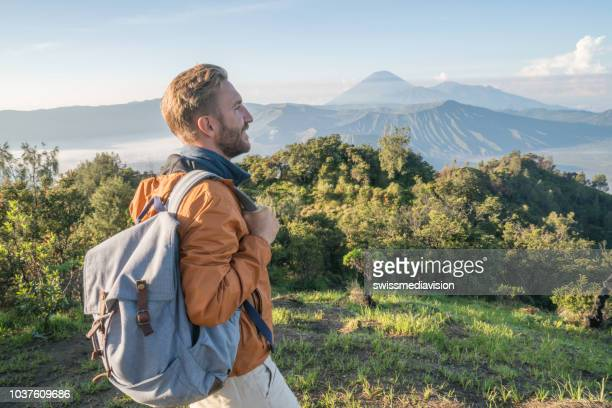 young man hiking contemplates volcanic landscape from top of hill looking at bromo volcanoes- people travel adventure concept - wonderlust stock pictures, royalty-free photos & images