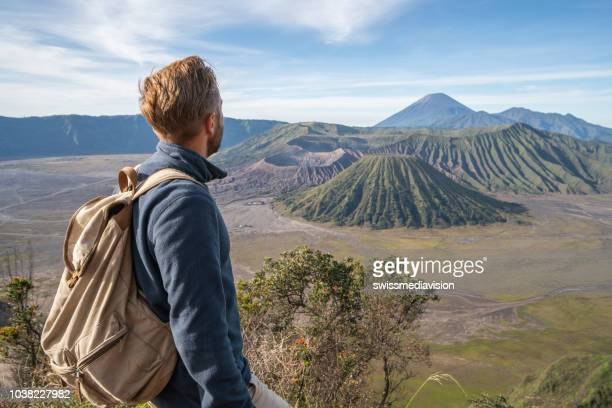 young man hiking contemplates volcanic landscape from top of hill looking at bromo volcanoes- people travel adventure concept - bromo tengger semeru national park stock photos and pictures