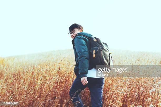 young man hiking in grassland - oost azië stockfoto's en -beelden