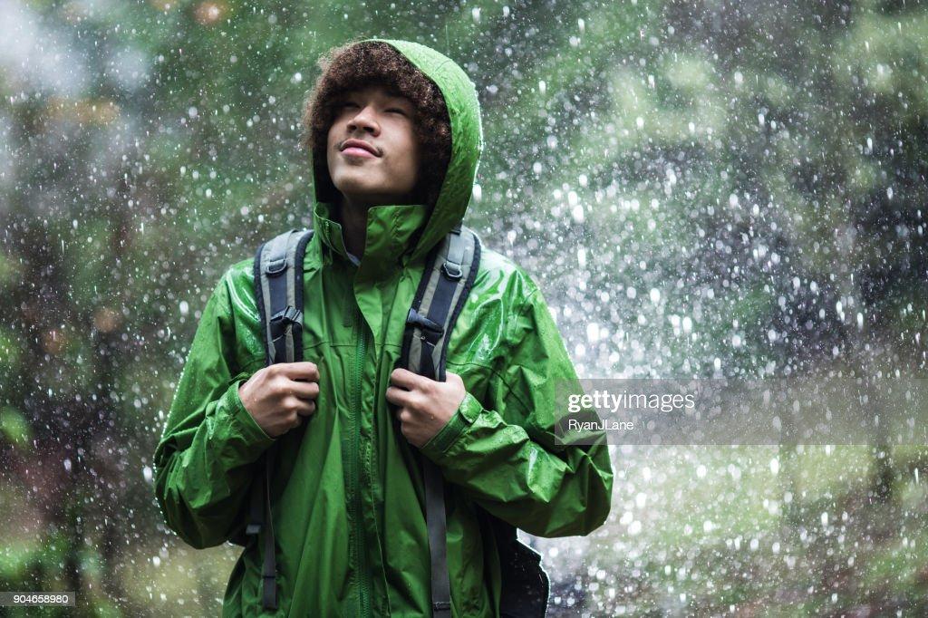 Senderismo en lluvia con chaqueta de hombre joven : Foto de stock