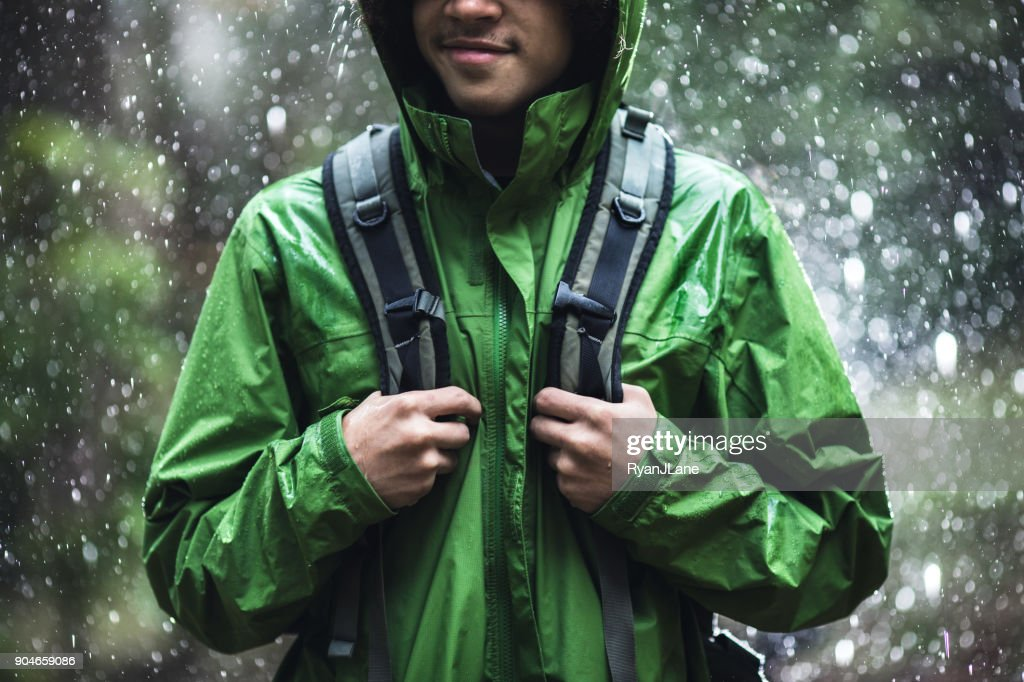 Young Man Hiking in Rain with Waterproof Jacket : Stock Photo