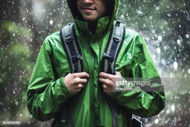 young man hiking in rain with waterproof jacket - giacca foto e immagini stock