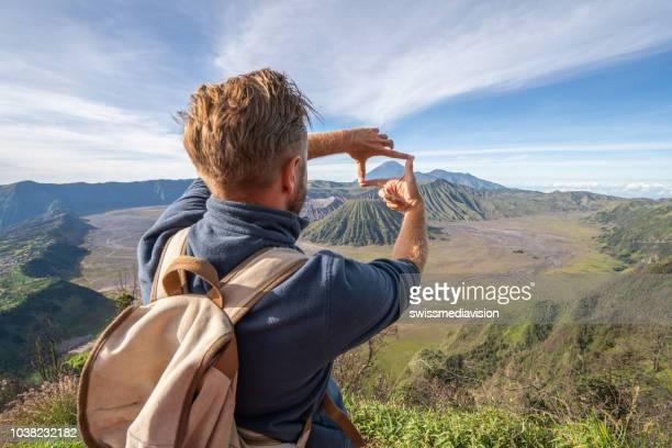 jovem caminhadas faz dedo frame na paisagem vulcânica do topo da colina olhando o conceito de aventura do bromo vulcões-pessoas viagens - dedos fazendo moldura - fotografias e filmes do acervo