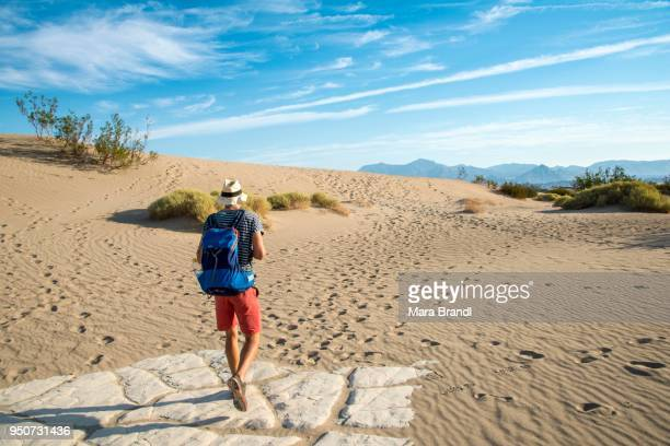Young man hiking on sand dunes, tourist, Mesquite Flat Sand Dunes, Death Valley, Death Valley National Park, California, USA