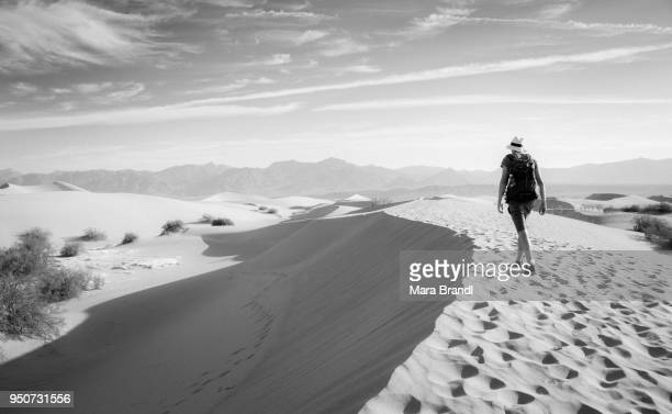 Young man hiking on sand dunes, tourist, Mesquite Flat Sand Dunes, foothills of Amargosa Range behind, Death Valley, Death Valley National Park, California, USA
