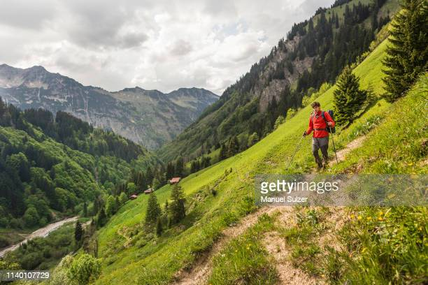 young man hiking on valley path, oberstdorf, bavaria, germany - oberbayern stock-fotos und bilder