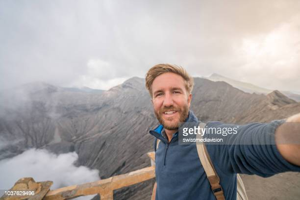 young man hiking on volcano takes selfie portrait with crater view- people travel adventure concept - bromo crater stock photos and pictures