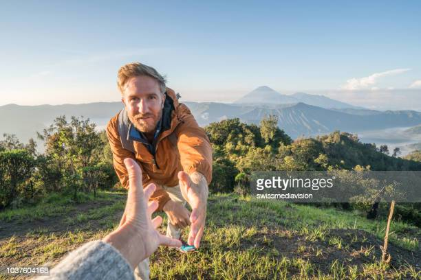young man hiking, pulls out hand to reach the one of teammate. a helping hand to reach the mountain top. bromo volcano region in indonesia, asia male getting assistance from partner - active volcano stock pictures, royalty-free photos & images