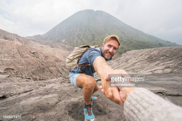 young man hiking, pulls out hand to reach the one of teammate. a helping hand to reach the top of crater volcano. bromo volcano region in indonesia, asia - fare da guida foto e immagini stock