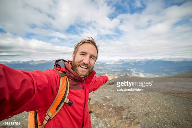 Young man hiking reaches mountain top and takes a selfie
