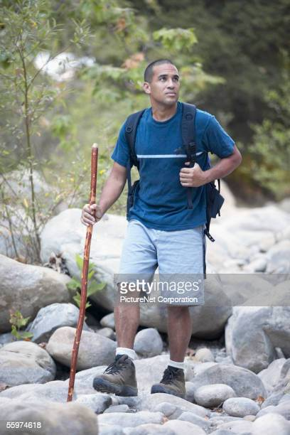 Young man hiking with walking stick