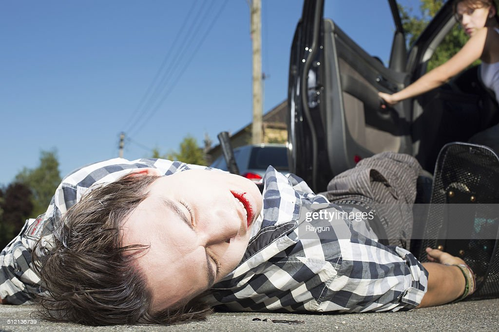 Young man hit by car lying on road : Stock Photo