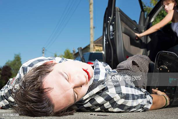 young man hit by car lying on road - bloody car accidents stock pictures, royalty-free photos & images