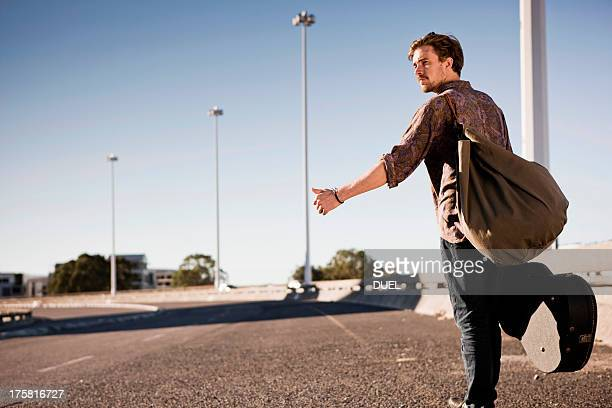 young man hitch hiking - guitar case stock pictures, royalty-free photos & images
