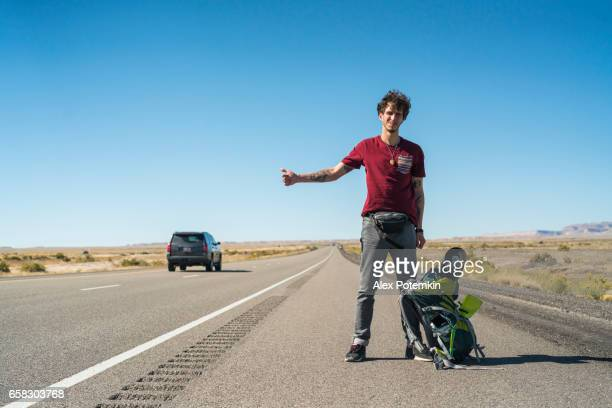 Young man, hitchhiker, looking for ride on highway, Utah desert