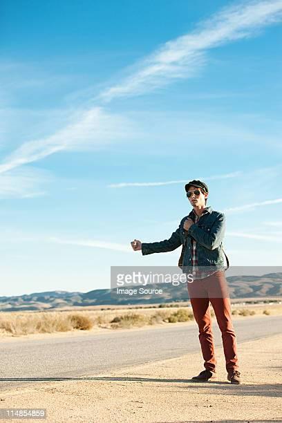 Jeune homme Faire du stop au bord de route