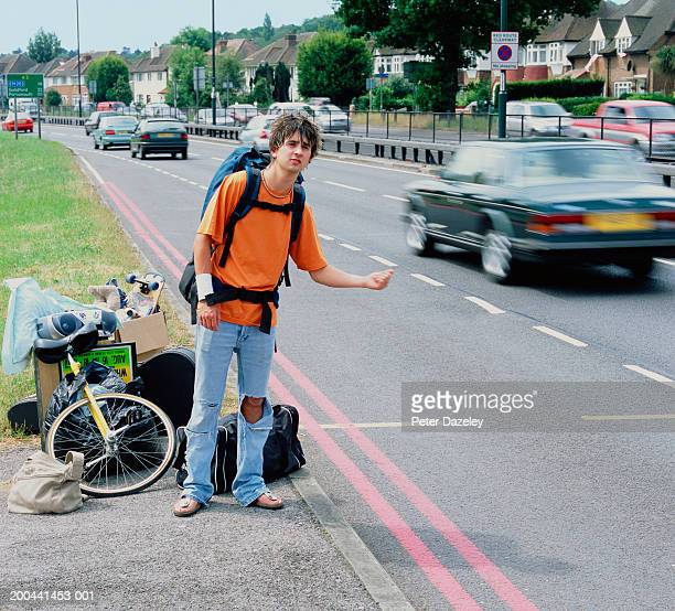 Young man hitchhiking with belongings