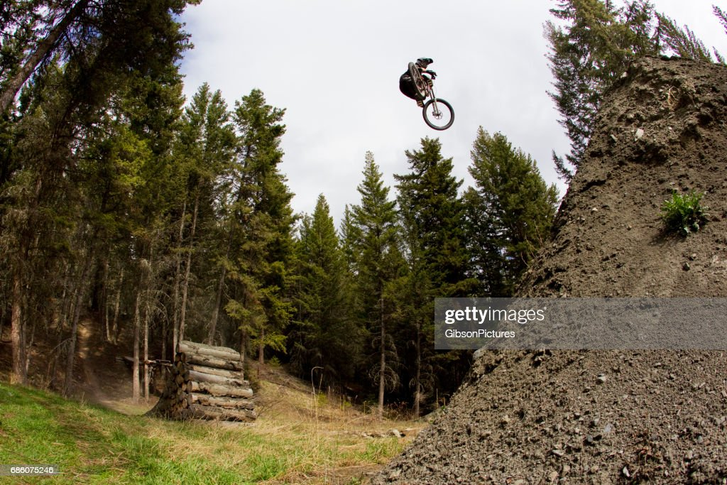 A young man hits a big jump on his downhill-style mountain bike. : Stock Photo