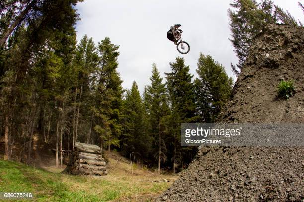 A young man hits a big jump on his downhill-style mountain bike.