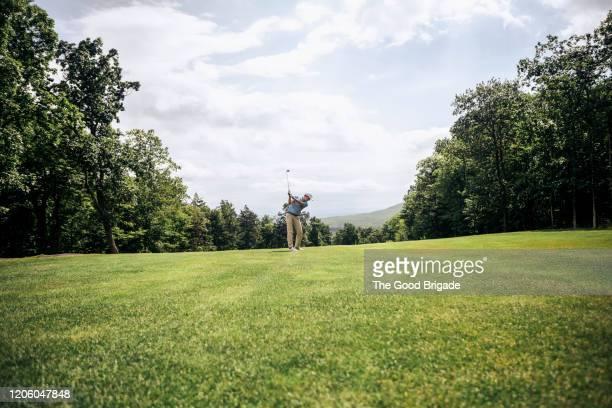 young man hitting a golf ball - ゴルフのスウィング ストックフォトと画像