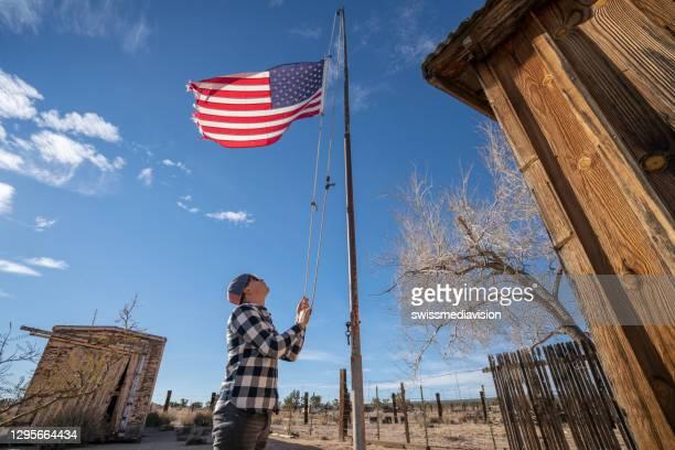 青空に対するアメリカ国旗を掲げる若者 - 吊り上げる ストックフォトと画像