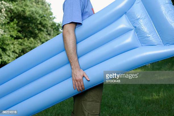 Young man holding a airbed