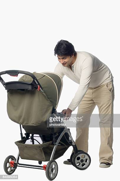 Young man holding a baby stroller