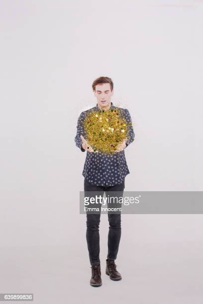 Young man holding a ball of glitter